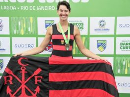 Atleta Yanka Britto segurando bandeira do Flamengo no pódio